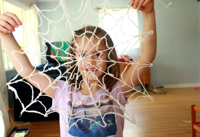 Maia holding yarn spiderweb